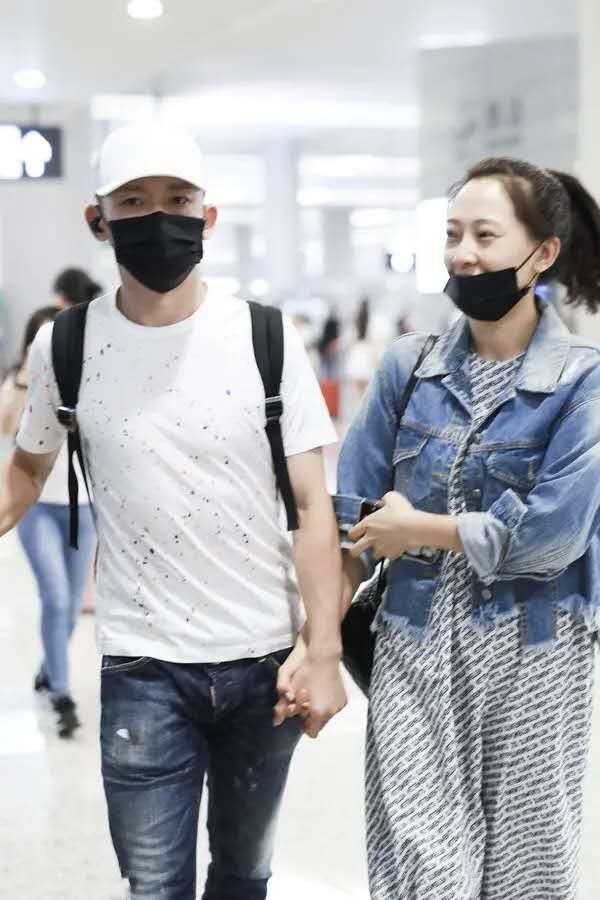 聂远携妻子走机场,穿T恤配牛仔裤很舒适,秦子越素颜五官真耐看