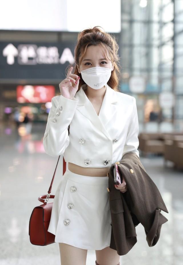 金莎翻红后高调走机场,穿白色短西装配短裙,红色长靴太有女人味