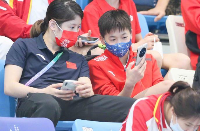 全红婵现身看台!目睹国家队师哥夺冠,戴卡通口罩,专注玩手机
